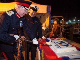 Lord Lieutenant of Dorset and Poole Lifeboat Station's Coxswain cutting cake at 150th anniversary